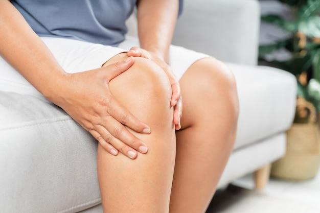 ソファに座って膝の痛みを感じ、膝をマッサージする女性ヘルスケアと医療