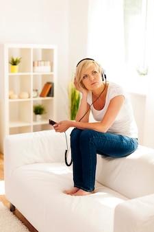 여자는 소파에 앉아 음악에 대해 궁금해