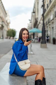 Женщина, сидящая на улице, звонит по телефону