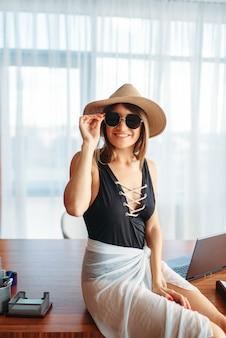 Женщина сидит на столе в офисе и думает о летних приключениях.