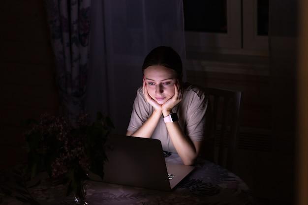 Женщина сидит на столе, смотрит фильм на ноутбуке поздно вечером, не может уснуть, делится соцсетями
