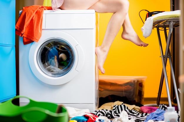 Женщина сидит на стиральной машине в прачечной. крупным планом вид на машину и ноги