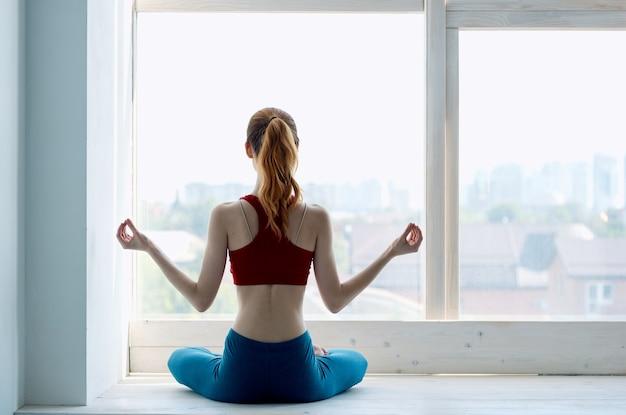 窓際の窓辺に座っている女性ヨガエクササイズスリムフィギュア