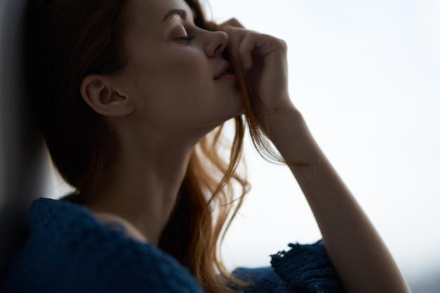 青い格子縞の朝と窓辺に座っている女性。高品質の写真