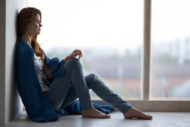 青い格子縞の休息のライフスタイルで窓辺に座っている女性