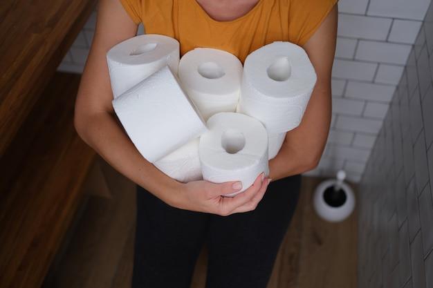 トイレに座って、紙のクローズアップの多くのロールを保持している女性