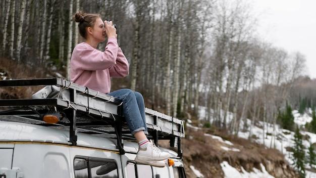 Женщина, сидящая на фургоне с полной камерой