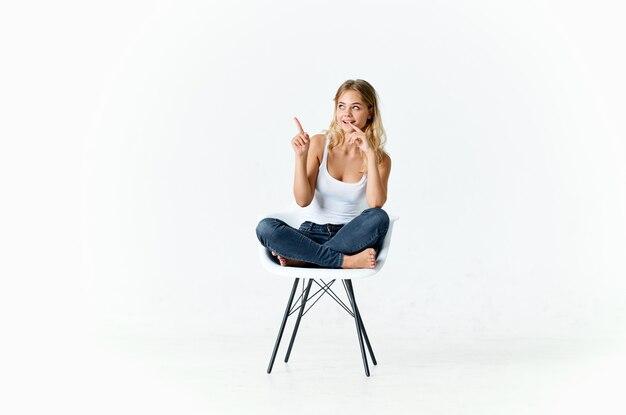 Женщина, сидящая на белом стуле с согнутыми ногами светлом фоне