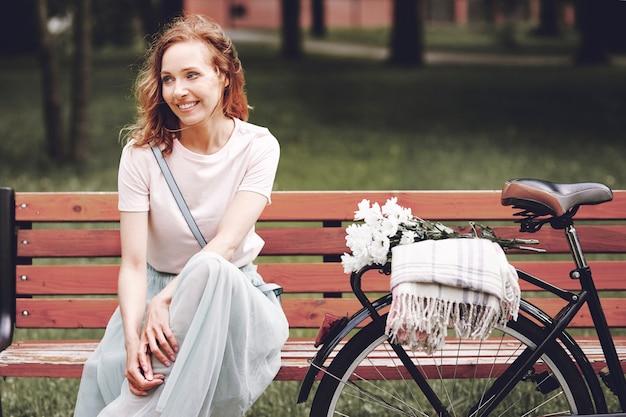公園の木製のベンチに座っている女性