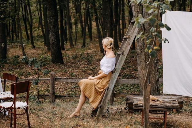 Женщина, сидящая на деревянной лестнице на заднем дворе
