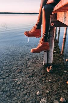 湖の上の木製の通路に座っている女性