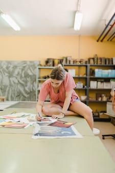 Женщина, сидя на верстаке, делая живопись на холсте бумаги в мастерской