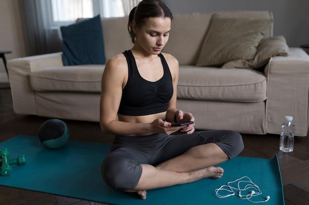 Женщина сидит на коврик для йоги и смотрит на телефон
