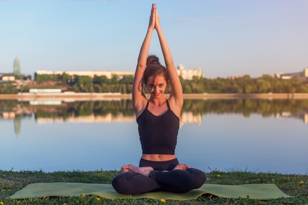 Женщина сидя outdoors размышляя в положении йоги около реки.