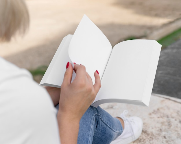 Woman sitting outdoors and reading book