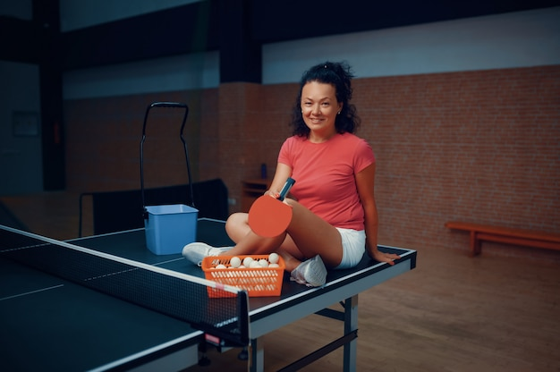 Woman sitting on ping pong table