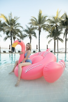 Woman sitting on pink inflatable mattress flamingos in the pool near the beach.
