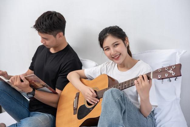 Una donna seduta suona la chitarra e un uomo tiene un libro e canta.