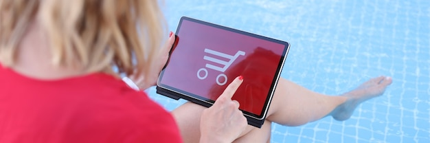 Woman sitting in pool makes online purchases on tablet