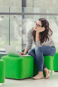 Woman sitting on pouf and using laptop