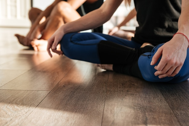Woman sitting and practicing yoga in group at studio