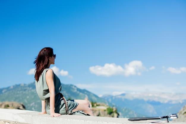 Woman sitting at precipice in greece