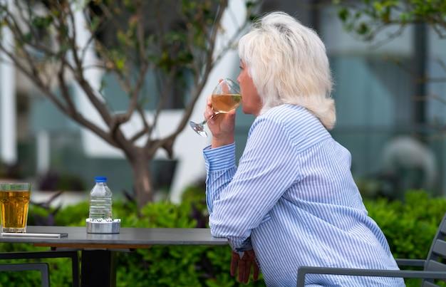 静かに座って白ワインをすする女性
