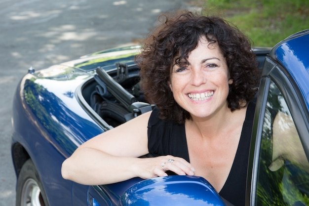 Woman sitting in retro cabriolet car in side frony view