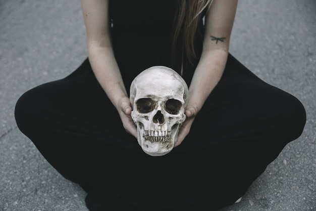 Woman sitting on road holding decorative skull of man between knees
