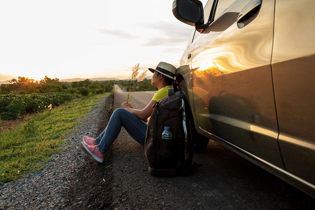 Woman sitting on the road at sunset with cars and backpacks concept of vacation and travel