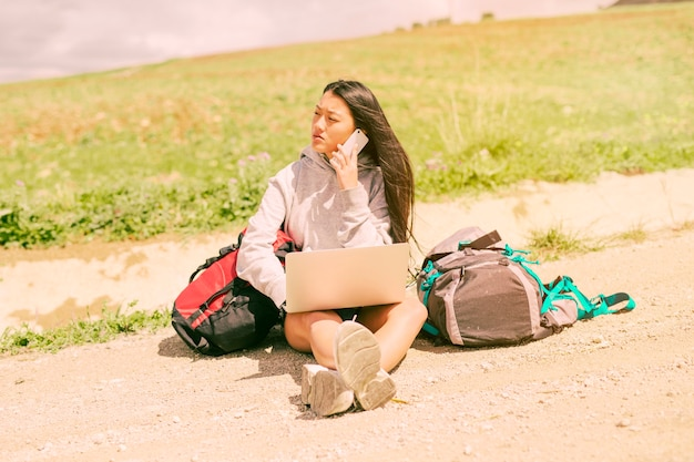 Woman sitting on road and talking on mobile phone among backpacks