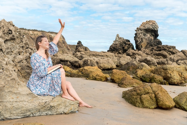 Woman sitting on a rock waving on the beach