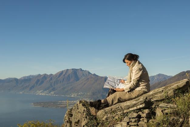 Donna seduta sulla roccia con una bellissima vista di una montagna vicino alla riva del mare