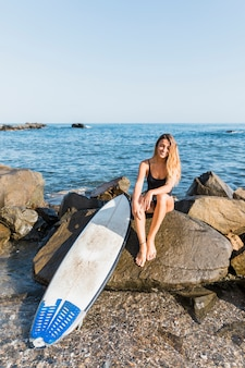 Woman sitting on rock with surfboard