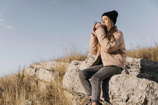 Donna seduta sulle rocce con tazza