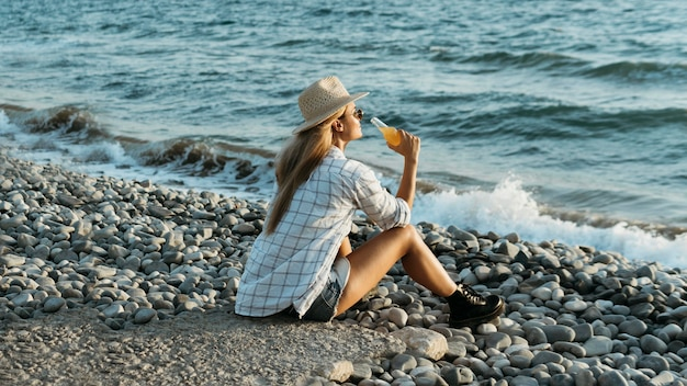 Woman sitting on rocks with juice looking at sea