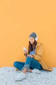 Woman sitting on rug listening music with headphones using cellphone