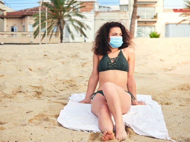Woman sitting on the sand on the beach sunbathing with a medical mask
