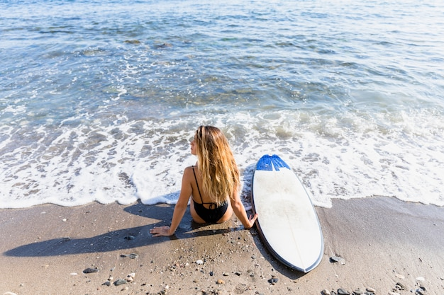 Woman sitting on sandy sea shore with surfboard