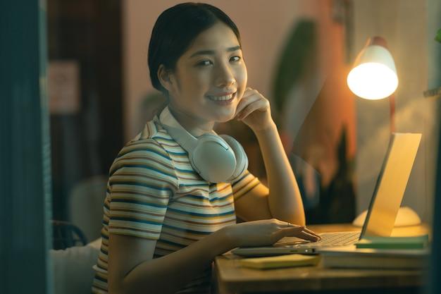 学校に座って、夕方に自宅で働く女性