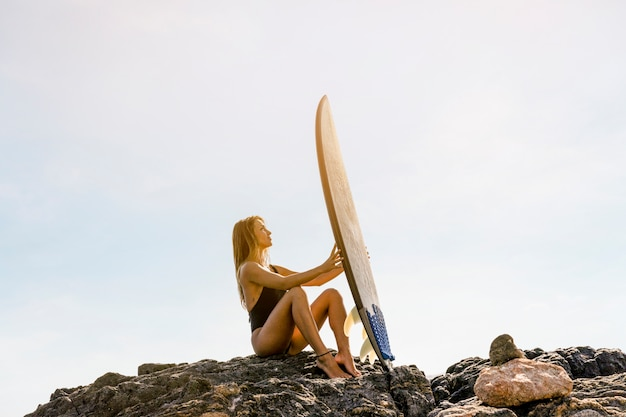 Woman sitting on sea shore with surfboard