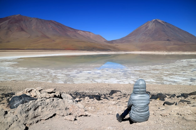 Woman sitting on the shore of laguna verde or the green lake, potosi, bolivia