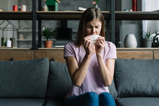 Woman sitting on sofa blowing nose with tissue paper