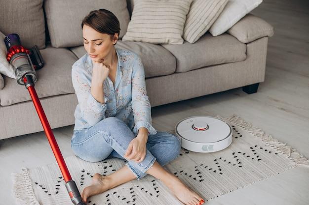Woman sitting on sofa and choosing vacuum cleaner