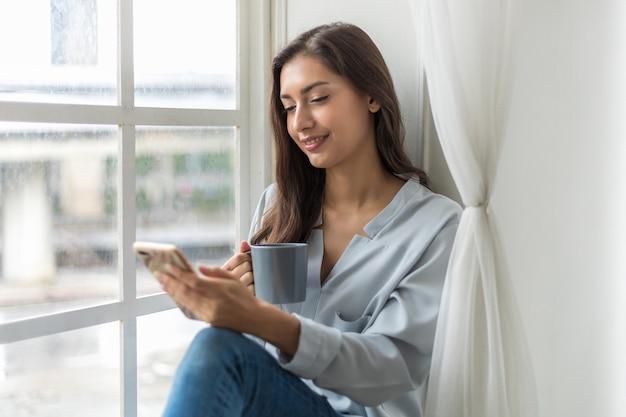 햇빛에 첫 모닝 커피를 즐기고 스마트폰을 사용하여 뉴스를 확인하는 소파에 앉아 있는 여성