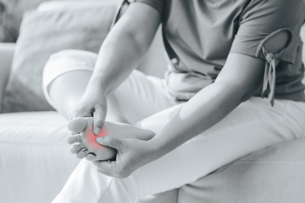 Woman sitting on the sofa and holds her foot suffering from foot pain with red highlight