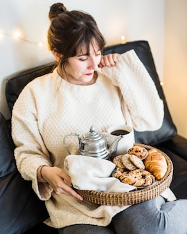 Woman sitting on sofa with food on tray