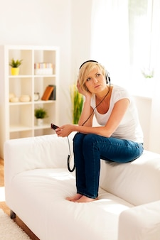 Woman sitting on the sofa and wondering about some music