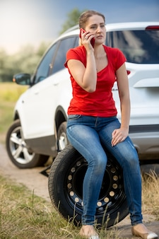 Woman sitting on the spare tire at roadside and calling for help