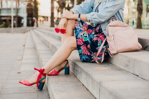 Woman sitting on stairs in city street in printed skirt with leather backpack holding sunglasses